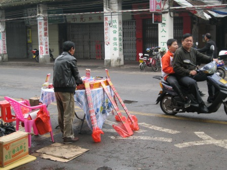Drive-up firework sales in Haikou; the father and son on the scooter completed a purchase a second before I snapped this photo.