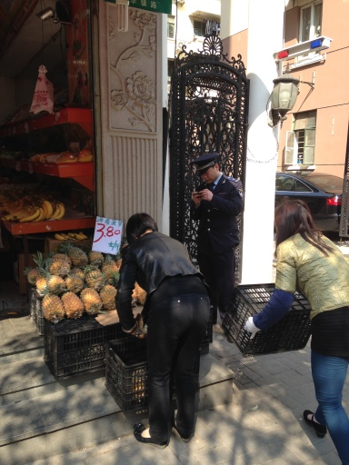 Women moving pineapples off the steps while the chengguan studies his cell phone.