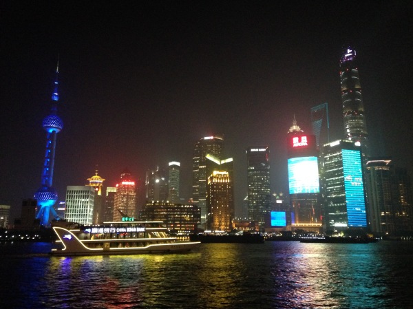 The skyscrapers of Pudong lit up in technicolor at night.